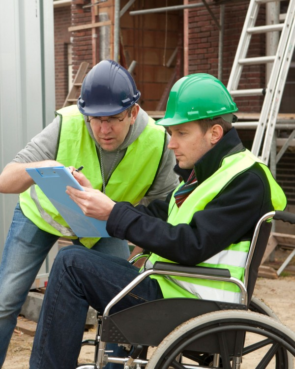 Two men wearing hardhats review a blue print. One man is seated in a wheelchair.