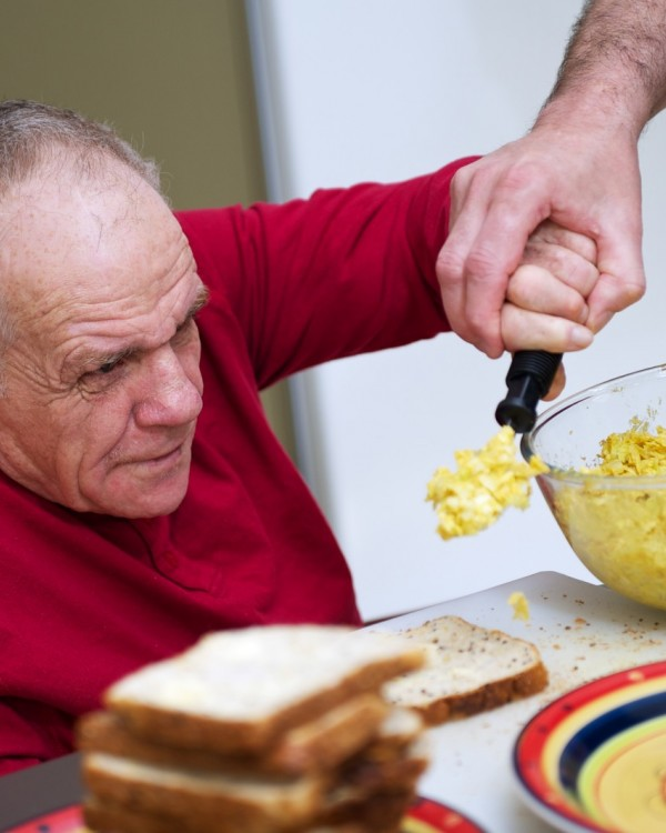 A senior man receives assistance using a fork to feed himself from his occupational therapist.