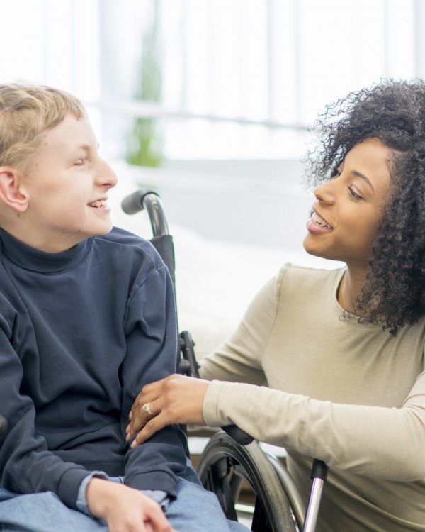 A young boy sitting in a wheelchair talks with his female OT.