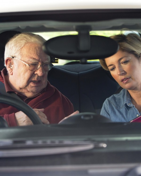 A senior man receives a driving assessment from his female OT.