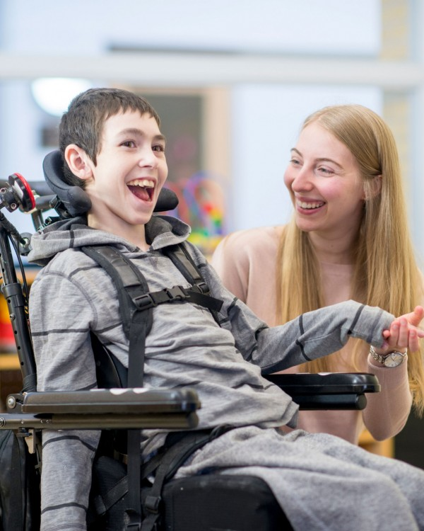 A young boy in a wheelchair and his female OT share a laugh.