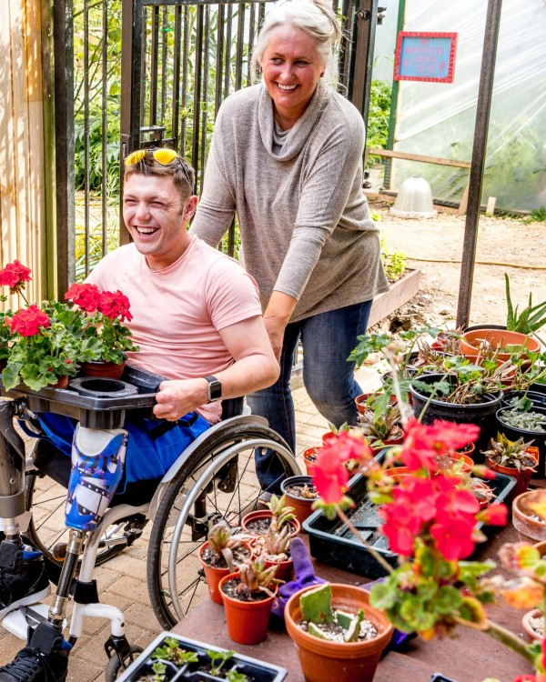 A young man sitting in a wheelchair holds onto potting geranium plants while his caregiver pushes his wheelchair through the garden centre.