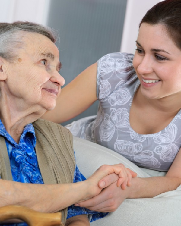 An elderly woman smiles at her OT who is holding her hand and smiling at her.